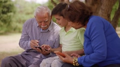 17-Boy Helping Grandpa Surfing Internet On Mobile Phone Stock Footage