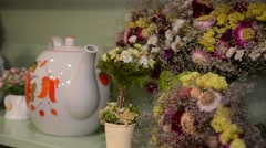 Flower bouquet displayed around teapot at a table setting Stock Footage