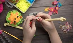 child hands are weaving figures out colored rubbers - stock photo