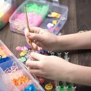 Child hands are weaving figures out colored rubbers Stock Photos