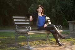 Portrait of one mature woman sitting on a bench. - stock photo