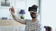 Man wearing virtual reality goggles. Studio shot, white couch - stock footage