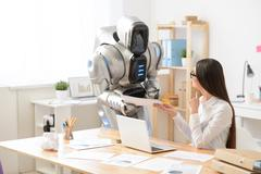 Pleasant girl and robot working in the office - stock photo