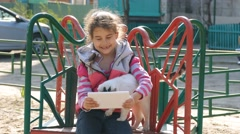 Girl playing in the tablet on the playground with a cat Stock Footage