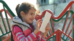 Girl teen with the tablet on the playground outddors Stock Footage