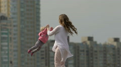 Mother rotating twisting making circle with her little daughter slow motion - stock footage