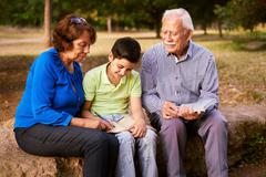 Grandpa And Grandma Helping Boy With Homework Stock Photos