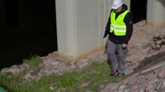 Engineer checking documentation near bridge construction - stock footage