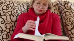 Senior woman sits on a sofa and flips through the pages of big book Stock Footage