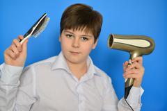 Boy teenager with comb and a hair dryer - stock photo