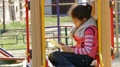 Girl teen with the tablet online game on the playground outddors Stock Footage