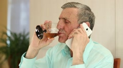 Man with cell phone sits at the table and drinks brandy Stock Footage