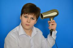 Boy teenager dries hair with hair dryer Stock Photos