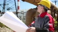 Worker in yellow hard hat with design drawings at heat station Footage