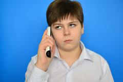 Teen boy talking by radiotelephony on a blue background - stock photo