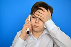 Upset teenage boy talking by radiotelephony Stock Photos