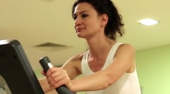 Woman trains in gym. Woman on exercise bicycle Stock Footage