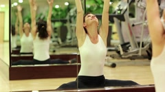 Woman trains in gym. Woman doing gymnastics in front of a mirror Stock Footage