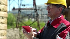 Emergency repairman with red smartphone at power station Stock Footage