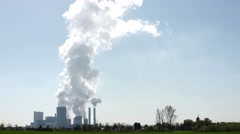 Coal-fired power station at a sunny day with blue sky and steam from cooling Stock Footage