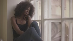 Beautiful and sad young african woman sitting on the windowsill and grieving Stock Footage