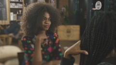 Two pretty elegant african females having coffee and talking in the cafe Stock Footage