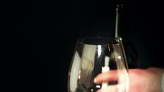Red wine from the bottle is poured into a glass Stock Footage