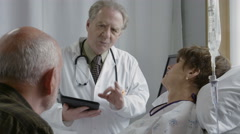 Doctor discussing medical procedure with older couple Stock Footage
