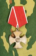Order of bravery on the camouflage background - stock photo