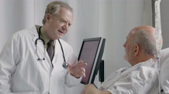 Physician talking with older male patient in the hospital - stock footage
