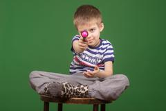Cute blond kid, playing with plastic pistol. Green screen background. - stock photo
