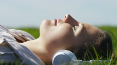 Young woman relaxing in the grass with her wireless headphones on a sunny day Stock Footage
