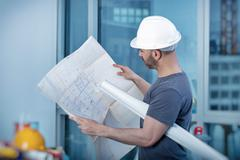 Architect builder studying layout plan of the room - stock photo