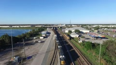 Aerial view from high to low of a freight train in the yard at Orlando, Florida - stock footage