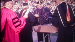 3212 students receive diplomas at graduation ceremony - vintage film home movie Stock Footage