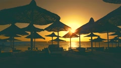 Parasol silhouette  on the beach of a tropical island at sunset Stock Footage