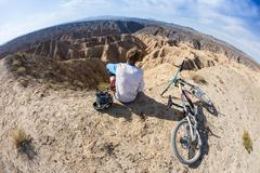 Young man on a mountain bike riding and relaxing in Charyn canyon, Kazakhstan Stock Photos