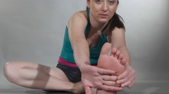 Young woman stretching in a yoga pose Stock Footage