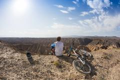 Young man on a mountain bike riding and relaxing in Charyn canyon, Kazakhstan - stock photo
