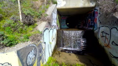 Graffiti storm drain tunnel with waterfall aerial tracking over creek Stock Footage