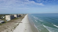 High aerial Northern view of waves crashing on the Ponce Inlet beach Stock Footage
