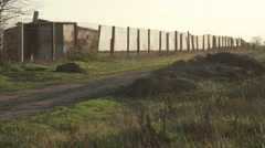 Pillars Hold Chain-Link Fence Beside Road at Which Pours Water From a Tank Stock Footage