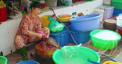 Local vendor scales a fish at an indoor public market in Ho Chi Minh City Stock Footage