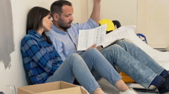 Sad, unhappy couple reading bills sitting on floor at their new home  Stock Footage