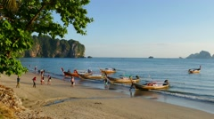 Long tail boats and tourists on Ao Nang beach Stock Footage