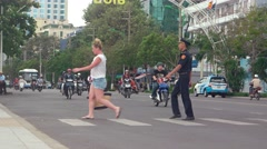 Tourist crossing a busy street in Nha Trang, with help from a traffic officer Stock Footage