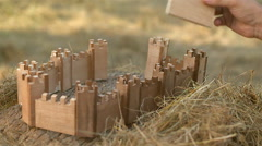 A man building a castle model Stock Footage