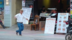 Restaurant greeter dances as he invites customers to dine in Nha Trang. - stock footage