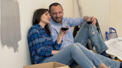 Young, happy couple raising toast and drinking wine on floor at their new home  Stock Footage