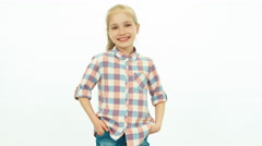 7-8 years old girl in the jeans and a shirt standing on the white background - stock footage